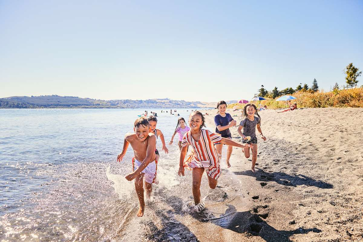 Kids running on 5 Mile Bay in Lake Taupo, New Zealand